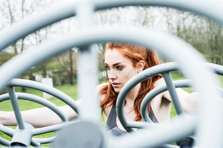 Young woman with long red hair wearing sports kit, using outdoor exercise machine.の写真素材 [FYI02266751]