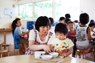 Female teacher sitting at table in a Japanese preschool, helping young boy to eat his lunch.の写真素材 [FYI02266754]