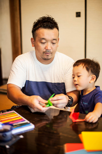 Japanese man and little boy sitting at a table, making Origami animals using brightly coloured paperの写真素材 [FYI02266759]