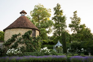 View of small round stone tower and pavilion from across a walled garden with trees and flowerbeds.の写真素材 [FYI02266760]
