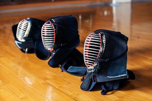High angle close up of row of three Kendo masks on hardwood floor.の写真素材 [FYI02266764]