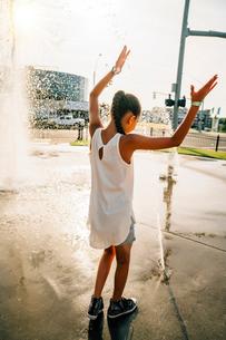 Girl playing in public fountain in summerの写真素材 [FYI02266779]