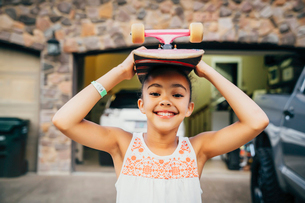 Smiling girl standing in driveway in front of house with skateboard on her headの写真素材 [FYI02266793]