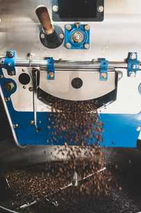 Close up of freshly roasted coffee beans pouring from coffee roaster.の写真素材 [FYI02266799]