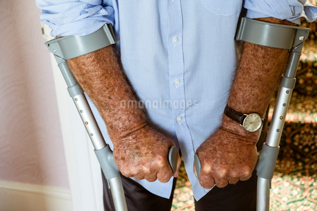 A man using crutches, with his weathered hands on the handles.の写真素材 [FYI02266809]