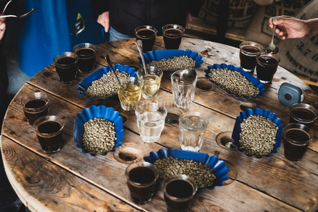 High angle view of glasses with coffee and trays with coffee beans standing on wooden table at a cofの写真素材 [FYI02266811]