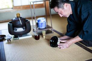 Japanese man wearing traditional kimono kneeling on floor, holding tea bowl, during tea ceremony.の写真素材 [FYI02266831]