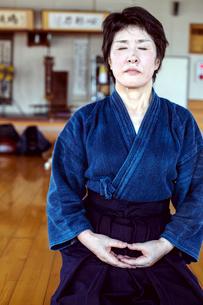 Female Japanese Kendo fighter kneeling on wooden floor, meditating.の写真素材 [FYI02266840]