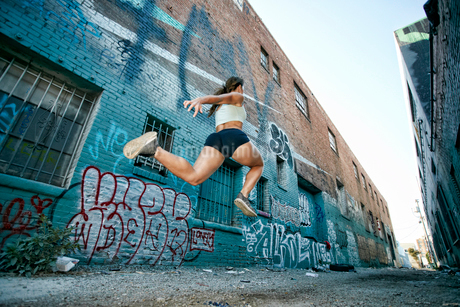 Female athlete running along street past blue building covered in graffiti.の写真素材 [FYI02266841]