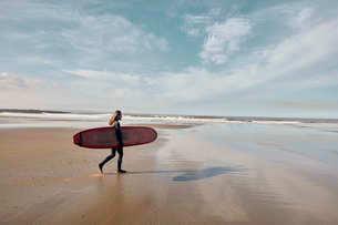 Man in a wetsuit walking towards sea holding a surf boardの写真素材 [FYI02266856]
