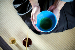 High angle close up of Japanese man wearing traditional kimono kneeling on floor holding blue bowl wの写真素材 [FYI02266860]