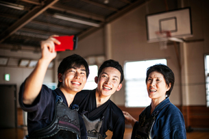Smiling female and two male Japanese Kendo fighters standing in a gym, taking selfie with mobile phoの写真素材 [FYI02266864]