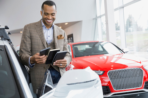 Man looking at color swatches in car dealershipの写真素材 [FYI02267232]