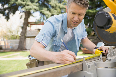 Man measuring wood plank at table sawの写真素材 [FYI02267341]
