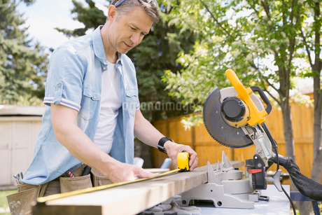 Man measuring wood plank at table sawの写真素材 [FYI02267490]