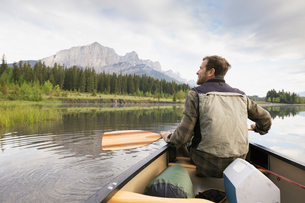 Man sitting in canoe in still lakeの写真素材 [FYI02268024]