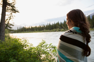 Woman wrapped in blanket looking at lake viewの写真素材 [FYI02268055]