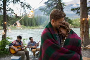 Couple wrapped in blanket hugging at lakeside campsiteの写真素材 [FYI02268072]