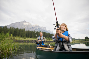 Father and son fishing in canoe in lakeの写真素材 [FYI02268333]