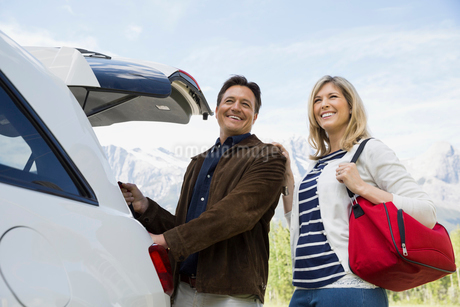 Smiling couple with luggage at carの写真素材 [FYI02268354]