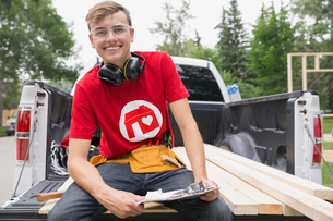 Portrait of smiling volunteer with clipboard on tailgateの写真素材 [FYI02268617]