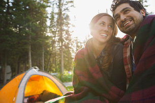 Couple wrapped in a blanket at campsiteの写真素材 [FYI02268619]