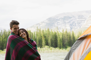 Couple wrapped in blanket at campsiteの写真素材 [FYI02268632]