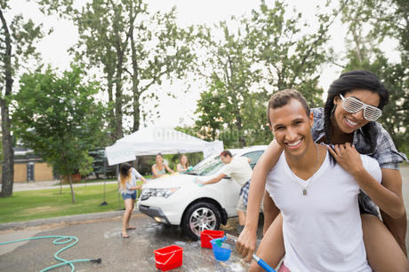 Portrait of smiling friends at car washの写真素材 [FYI02268843]