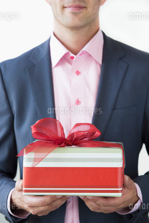 Well-dressed man holding Christmas giftの写真素材 [FYI02268913]