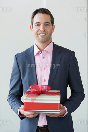 Portrait of well-dressed man holding Christmas giftの写真素材 [FYI02269012]