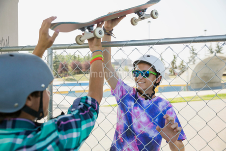 Teenage boys passing skateboard over fenceの写真素材 [FYI02269323]