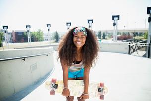 Portrait of teenage girl holding skateboardの写真素材 [FYI02269335]
