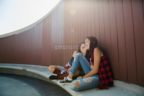 Teenage girls whispering on benchの写真素材 [FYI02269347]