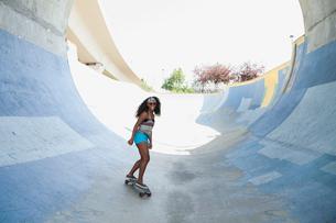 Teenage girl skateboarding at skateboard parkの写真素材 [FYI02269736]