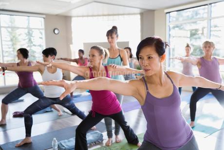 Women practicing warrior 2 pose in yoga classの写真素材 [FYI02271307]