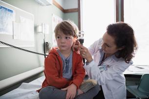 Pediatrician checking ear of boy in examination roomの写真素材 [FYI02271323]