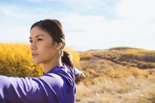 Woman practicing yoga in sunny rural fieldの写真素材 [FYI02271415]