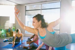 Woman practicing king dancer pose in yoga classの写真素材 [FYI02271434]