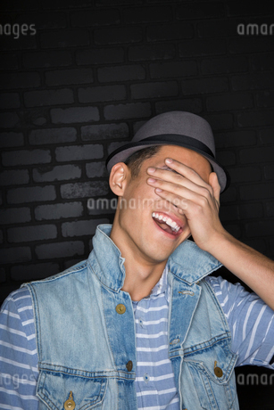 Laughing man in fedora covering eyesの写真素材 [FYI02272349]