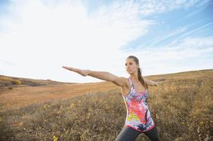 Woman practicing yoga in sunny rural fieldの写真素材 [FYI02272564]