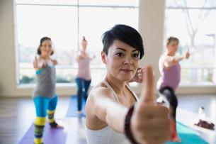 Women practicing warrior 2 pose in yoga classの写真素材 [FYI02272590]