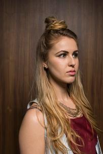 Pensive blonde woman with hair bun looking awayの写真素材 [FYI02272649]