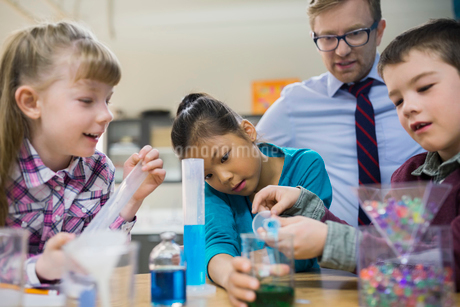 Teacher and elementary students conducting scientific experimentの写真素材 [FYI02272659]
