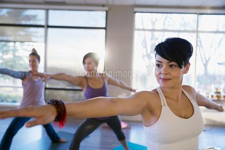 Women practicing warrior 2 pose in yoga classの写真素材 [FYI02272660]