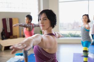Women practicing warrior 2 pose in yoga classの写真素材 [FYI02272680]