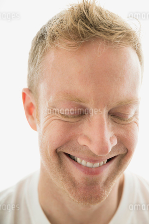 Close up smiling blonde man with eyes closedの写真素材 [FYI02272692]