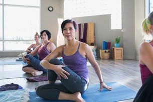 Women practicing seated twist pose in yoga classの写真素材 [FYI02272792]