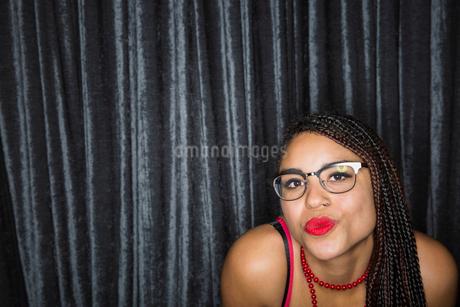 Portrait of flirtatious woman with braids puckeringの写真素材 [FYI02272898]
