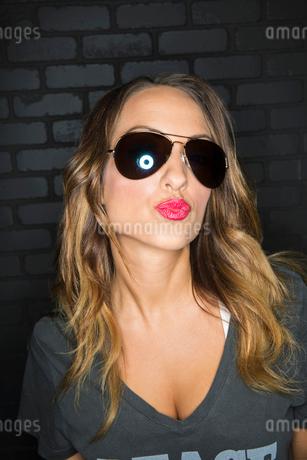 Portrait of flirtatious woman wearing sunglasses puckeringの写真素材 [FYI02272938]