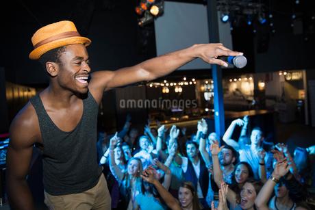 DJ with microphone above cheering nightclub crowdの写真素材 [FYI02273046]